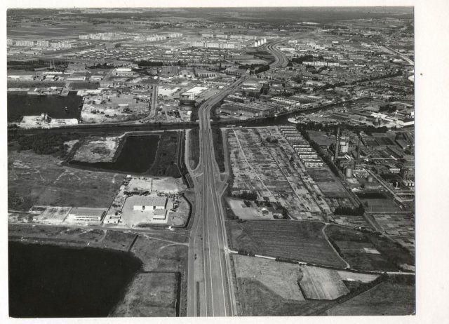 1969: Noordelijke Rondweg. Gezien vanuit het westen. Links de Emerput met rechts van de Backer en Ruebweg het bedrijf bedrijf AKU. Na de Charles Stulemeijerbrug over rivier de Mark ligt aan de linkerzijde de gashouder en aan de rechterzijde de Backer en Ruebfabriek met daarachter de watertoren aan de Speelhuislaan