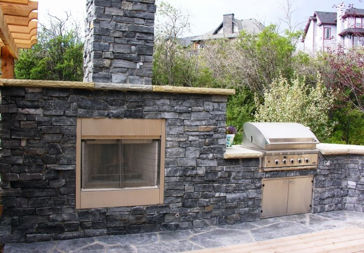 The perfect addition to a custom kitchen. This elaborate outdoor fireplace is perfect when cooking outside in the cooler months or for enjoying a night under the stars. #outdoorfireplace #backyardlandscaping