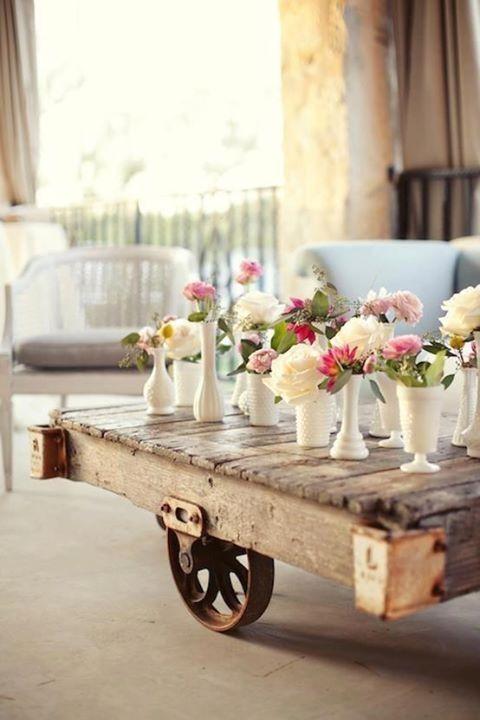 Mesa rústica de centro, con caja de frutas de madera, 2 ruedas de hierro recicladas como sostenedores (patas) y decorarla con floreros blancos pequeños de diferentes tamaños, para que contrasten y con unas flores cada uno.