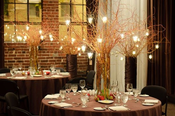 Fruits and creative twigs hanged with candles as table centerpiece.
