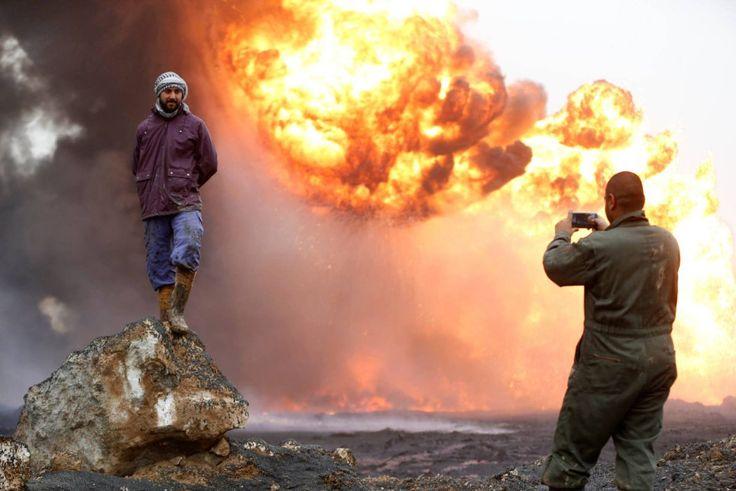 Un hombre hace una fotografía a su amigo frente a una explosión provocada por el Estado Islámico de un pozo petrolífero antes de huir de la región Qayyara (Irak), el 29 de enero.