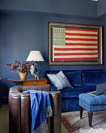 In a Manhattan apartment decorated by Phoebe Howard, study walls painted Benjamin Moore's Newburyport Blue set off a striking Civil War-era flag from Jeff Bridgman Antiques.
