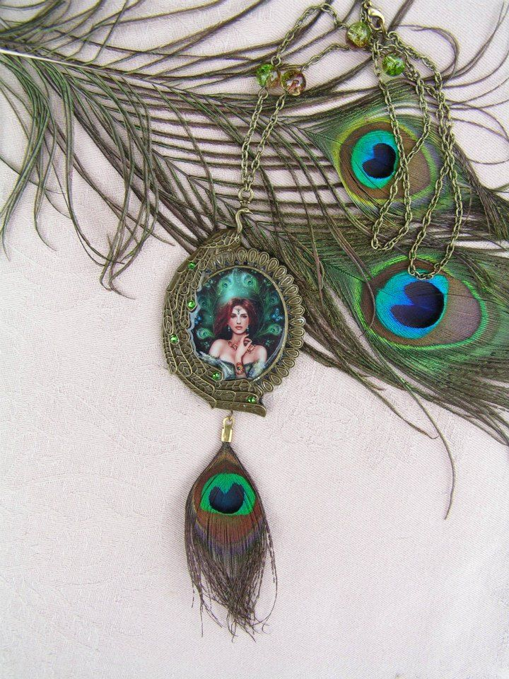 Juno Regina  --    I used the image of the goddess Juno to this large, peacock decorated pendant. I decorated the peacock tail-feathers with tiny Swarovski crystals to give back the beauty that the feathers represent.  The necklace is completed by a eal peacock feather and some matching shades of green and brown glass beads.