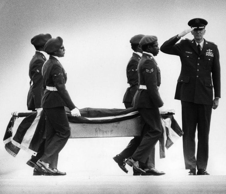 guards carrying the remains of Christa McAuliffe from a plane to a hearse at Dover Air Force Base following the loss of the Space Shuttle Challenger on January 28, 1986