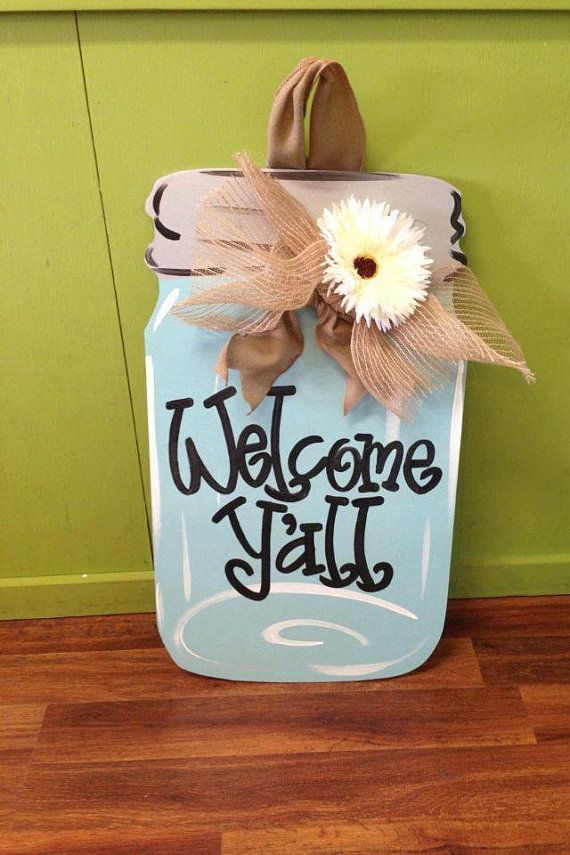 """Welcome guest with this awesome """"Welcome Y'all"""" Mason Jar Door Hanger!  Measuring 28"""" long x 18"""" wide this hand painted, wooden door hanger is perfect to welcome guests on the front door, poolside, or beachside.  Unique and one of a kind.  Features hand-painted jar, burlap bow, and gerbera daisy flower."""