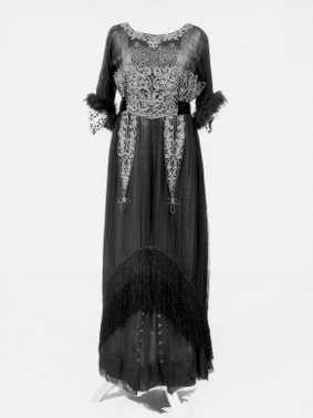 14-11-11  CMU  Japon (1911)  Zwart zijden crèpe-chiffon over ivoorkleurig zijden satijn, garnering van apenbont, zilverkleurige en witte machinale kant, groen zijden fluweelband, kwast van zilverkleurig metaaldraad, zwarte geknoopte zijden franje.