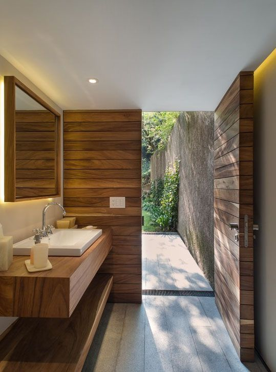 Unique bathroom design. Crisp modern shapes, minimal fixtures, warm tones from the natural materials and clean flooring style that leads out into the garden space. I love it! Bathroom heaven <3