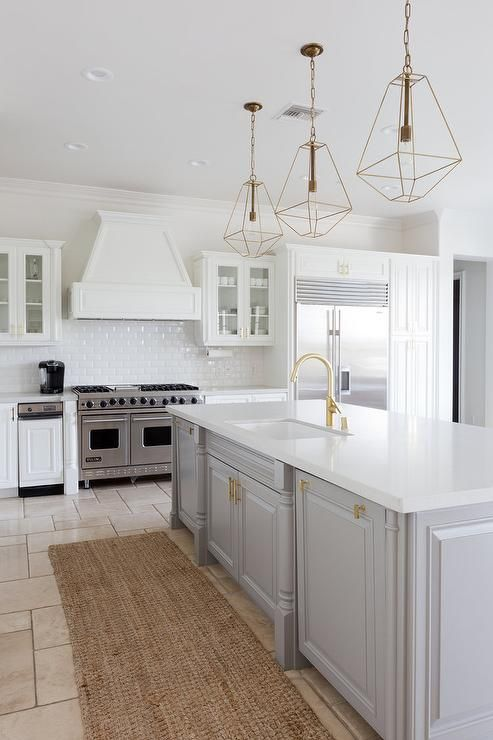 Well appointed gray and white kitchen is fitted with a jute runner placed  in front of a gray center island adorning brass pulls and a white quartz ...