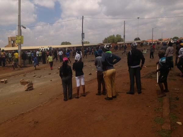 #Bekkersdal protests | Protesters watch as police rush a man -- allegedly shot by a shop owner -- to hospital. Photo: Andrea van Wyk ‏@Andrea / FICTILIS Wyk
