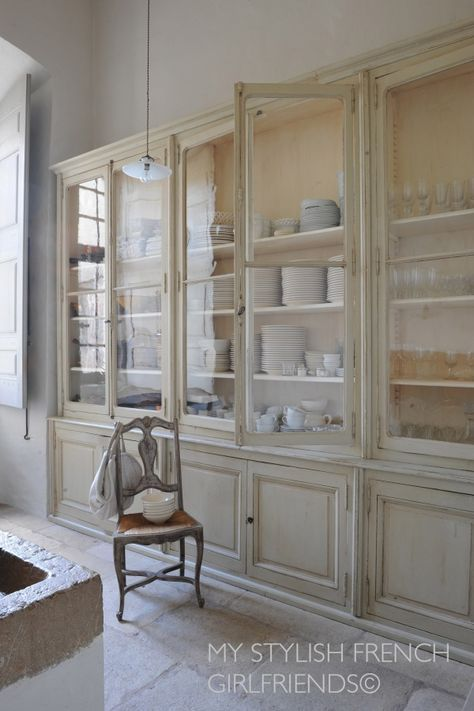 antique kitchen cabinetry with glass doors and very high ceilings