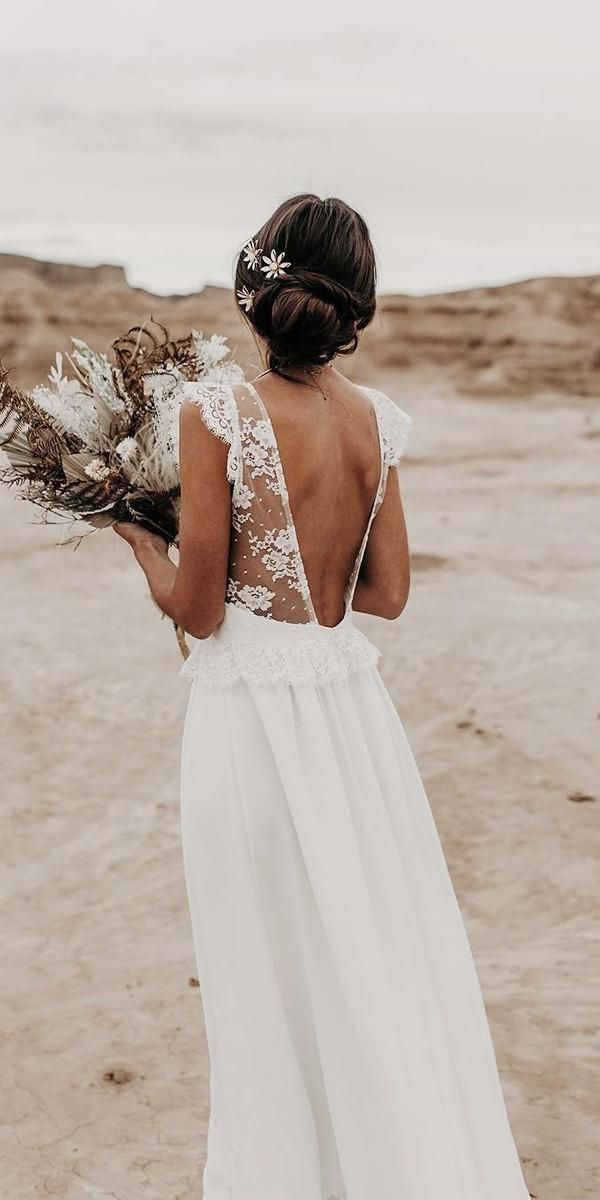 Open back wedding dress with sheer lace straps and large waterfall bouquet with …