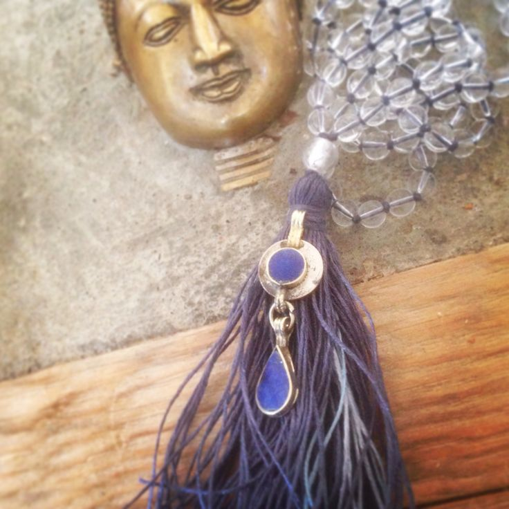 Unique & beautiful mala handmade with love & intention from clear quartz crystal beads & a reclaimed white glass guru bead woven over beautiful indigo coloured organic linen yarn. The mala is adorned with a lovely antique Kuchi coin pendant with lapis lazuli. Made by Shinseina Jewellery x