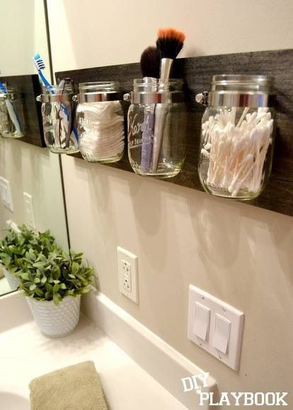jars bracketed by pipe wrap hung on a piece of stained/varnished wood -- for organizing toiletries and such in the bathroom
