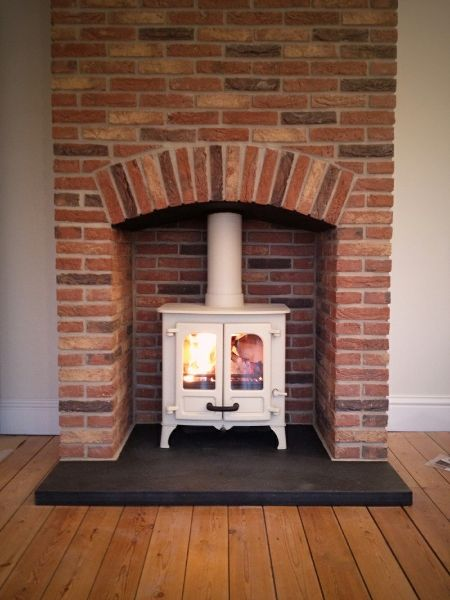 Charnwood Island 1 in almond on slate hearth with brick fireplace.