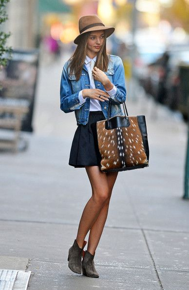 Miranda Kerr wearing a blue denim jacket, brown fedora hat and a animal fur handbag.