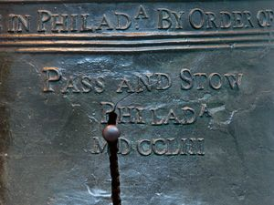 """Color photo showing a detail of the Liberty Bell focusing on a thin crack growing out of a much larger crack in the """"P"""" of """"Phila"""" on the bell."""