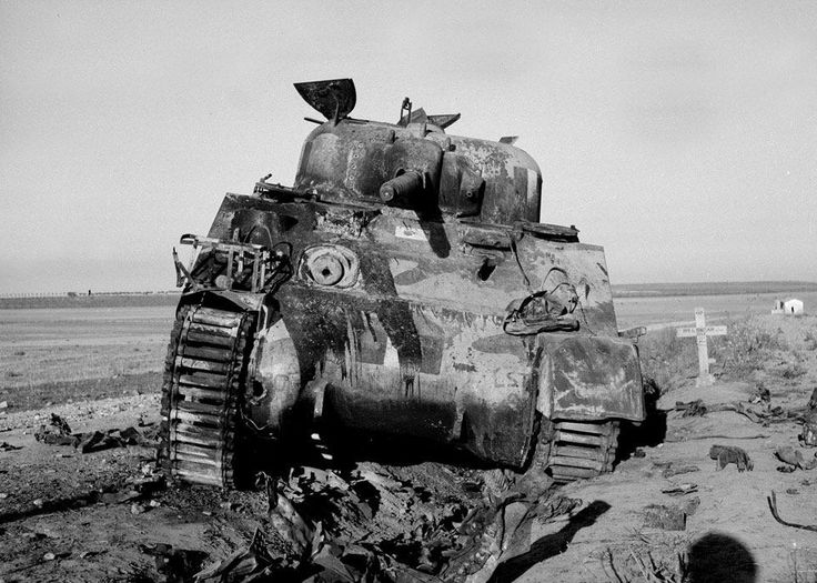 """The first casualty, Italy, September 1943. A knocked-out Sherman tank of 3rd County of London Yeomanry belonged to Norman Seddon. His tank was hit by a 75mm anti-tank gun at Coursa near Manfredonia on the road to Bari, killing one of the crewmen. The wooden grave marker visible to the right of the photograph is inscribed, """"R.I.P/ TPR G. SINCLAIR 7966645/ 3CLY/ KIIA/25.9.1943"""""""