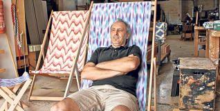 Rafel Picornell junto a sus tumbonas de madera con telas de ´llengües´.