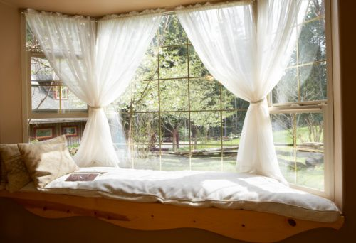 Sheer curtains in a bay window with pillows and cushions.