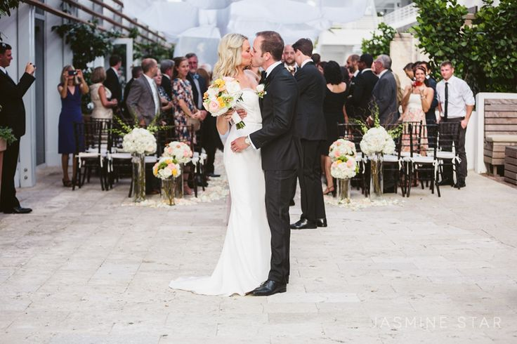 LOVE THIS POSE!  Have the guests stay at their seats and get a kiss as exiting the wedding.