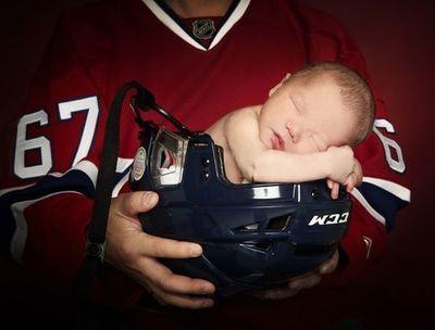 Newborn baby boy in his Daddy's hockey helmet