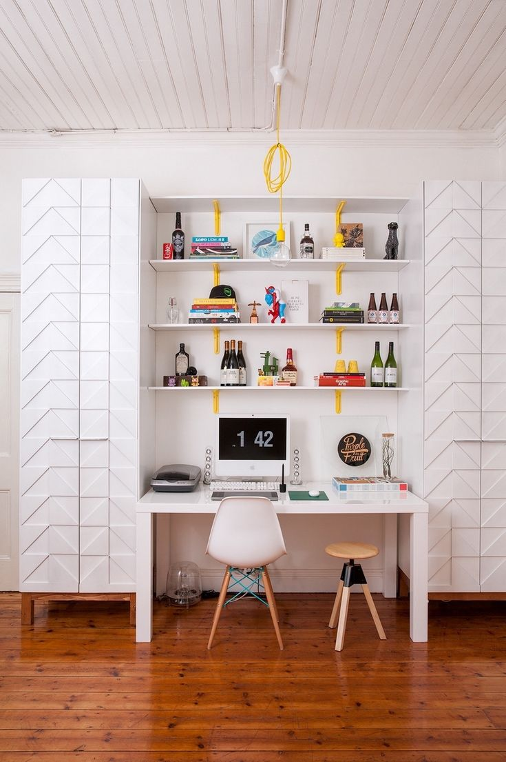 colonnes de rangement minimalistes et accents jaunes dans le bureau à la maison