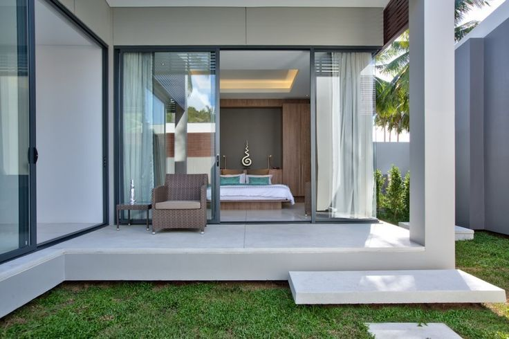 Hotels & Resort, Appealing Beach Villa Exterior Design With White Color Scheme Glass Window Big Tile Marble Floor Single Sofa And Green Grass Courtyard Open Bedroom Pillow Wooden : Beach Villa Design in Open and Natural Concept besides Sea Panorama