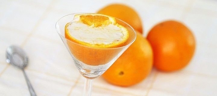 Gezond en slank grieks nagerecht van sinaasappel gevuld met fruitsmoothie