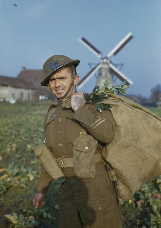 CHRISTMAS WITH THE BRITISH LIBERATION ARMY IN HOLLAND, NOVEMBER 1944. A unit postman with a sack of Christmas parcels decorated with holly near Weert.