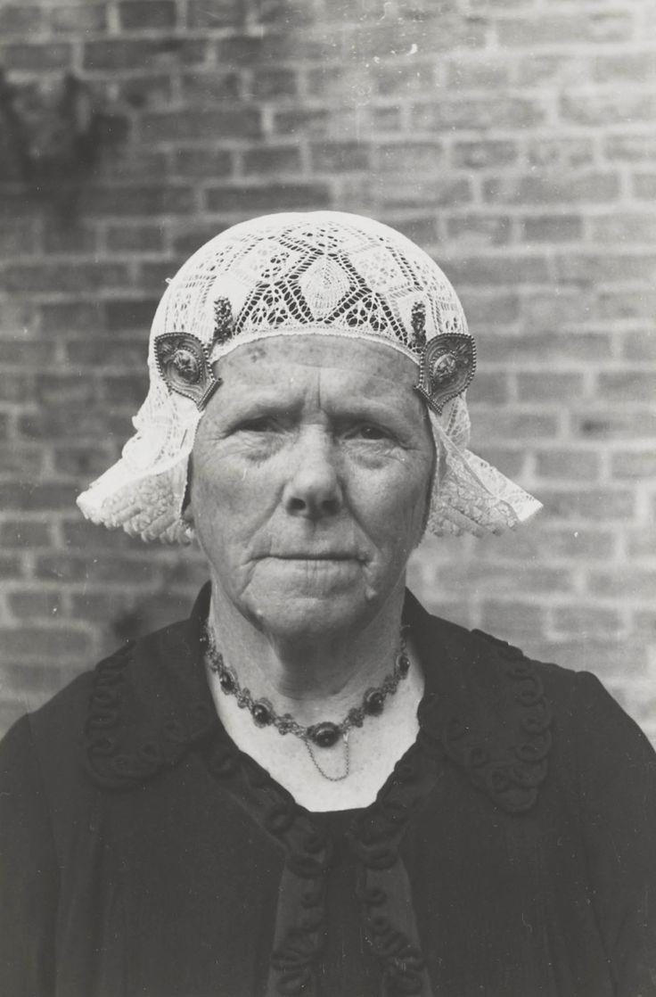 Weduwe Goslinga uit Workum, in Friese streekdracht. Mevrouw Goslinga draagt over het oorijzer een muts van fijn breiwerk. Om haar hals draagt ze een bootjesketting. ca 1943 #Friesland