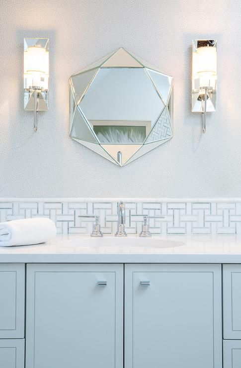 Calming light blue kid's bathroom showcases a stunning faceted mirror flanked by mirrored sconces mounted on a light gray wall above white and blue mosaic backsplash tiles lining a white quartz countertops sit atop a light blue washstand fitted with an oval sink with a polished nickel faucet.