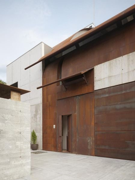 Studio Sitges, a working and living space for two artists in Sitges, Spain, designed by Olson Kundig Architects. Large steel panels arch from the ground over the entrance, curving to create part of the roof. Photo by Nikolas Koenig.