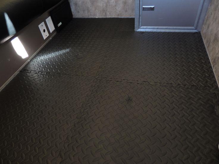 Plancher en tapis casse-tête que j'ai ajouté par dessus le plancher d'aluminium.  Facile d'entretien, confortable et garde les pieds au chaud.