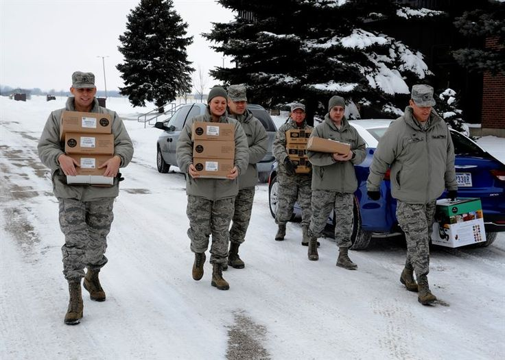 Members of the 319th Air Base Wing chapel team and wing leadership carry coffee supplies Dec. 30, 2015, on Grand Forks Air Force Base, North Dakota. The chapel team delivered eight Keurig coffee makers and 10 pallets of Keurig K-cups to different units. The coffee and machines were donated to Grand Forks AFB. (U.S. Air Force photo by Airman 1st Class Ryan Sparks/Released)