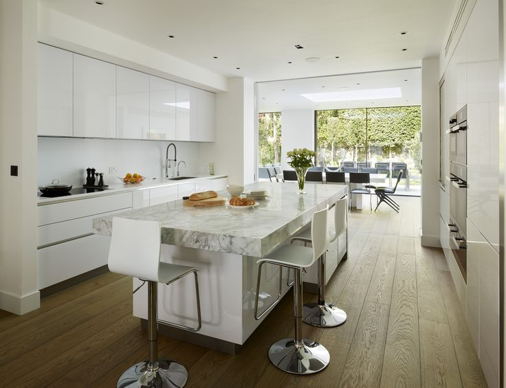 This elegant and minimalist family kitchen featuring Miele appliances was designed by Eve Turner of Neil Lerner Kitchen Design. The striking central island was created primary for dining and food preparation, maximising the use of this sociable open plan space #kitcheninspiration
