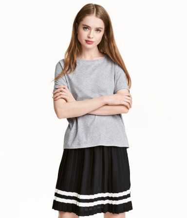 Black. Short, pleated skirt in woven fabric with an elasticized waistband and printed stripes at hem.