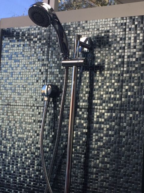 Hand shower featured in our showroom. Mosaic tiles