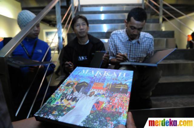 Dua pewarta foto Antara Saptono Soemardjo dan Prasetyo Utomo menandatangani buku bertajuk 'Makkah: Photographic Diary' saat peluncuran buku dan pameran foto di Galery Antara, Jakarta (03/08).