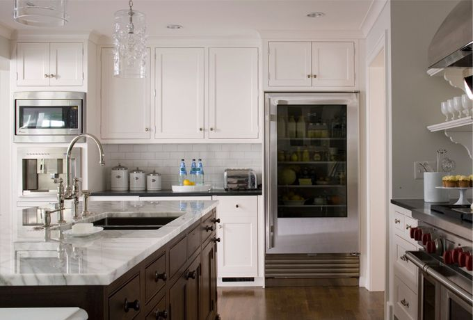 A Classic White Kitchen Featuring High-end Appliances-Calcutta Countertops And Honed Black