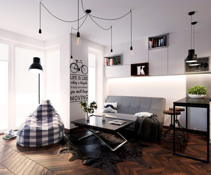 Love words and pictures? This space combines the two, in a Scandinavian feel. Trademark white walls in the living room are met with gingham bean bags and spider lights in this lounge, while an inspirational quote centres the wall. Black and white features play off one another in large lettering, moustache cushions and a solid black table. A grey couch on zigzagged wooden flooring sets the stage.
