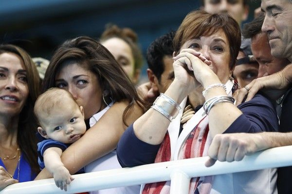USA's Michael Phelps' mother Deborah (R) and partner Nicole Johnson holding Michael Phelps' son, Boomer cry during the podium ceremony of the Men's swimming 4 x 100m Medley Relay Final at the Rio 2016 Olympic Games at the Olympic Aquatics Stadium in Rio de Janeiro on August 13, 2016.   / AFP / Odd ANDERSEN