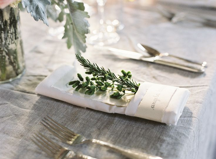 Folded napkin plate setting with tucked in greens + linen tablecloth