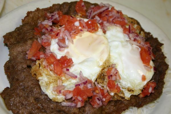 Bolivian Food silpancho  it tradition dish with rice breaded meat with 2 eggs and with tomatoes and onions