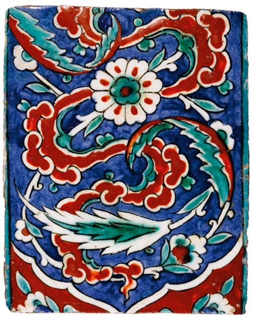 167 A POLYCHROME IZNIK TILE, TURKEY, 16TH CENTURY decorated in relief iron red and viridian green outlined in black with a design of stylised cloud bands and between scrolling saz leaves and rosettes on an underglaze cobalt blue ground 19.5 by 15.5cm. Sold at Sotheby's (2014) for 6,250 GBP