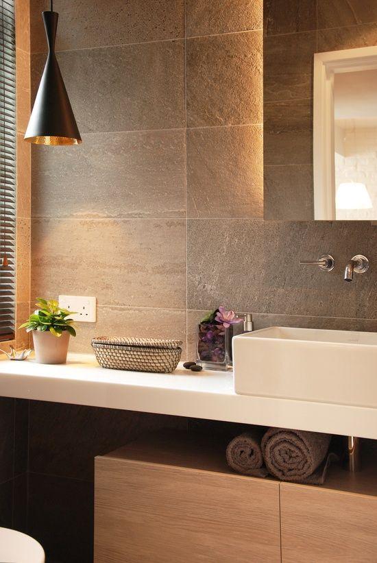 Banheiro bancada branca, cuba de sobrepot e cerâmica com acabamento semelhante a concreto.