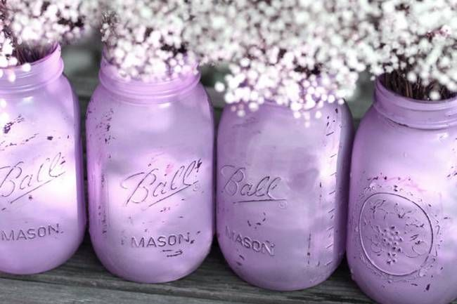 Marvelous mason jars distressed with lilac paint for a rustic or shabby chic style, great as wedding centrepieces!