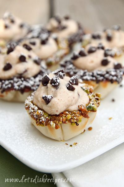 Chocolate Chip Cannoli Bites ~ Ingredients: Filling: 1 15oz container whole milk ricotta cheese, 3/4 C powdered sugar + for dusting, 1 tsp cinnamon, 1/8 tsp allspice, 1/4 C heavy cream, 1/4 C mini choc chips + for garnish, 2 tsp lemon zest. Phyllo cups: 2 pkgs Athens mini phyllo shells, thawed, 1 C choc chips, 2/3 C chopped pistachios.