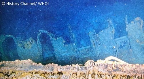 A recent photo of the outer wall of the gymnasium on the wreck of Titanic. The gymnasium has collapsed in recent years, with the roof caving in the half the outer walls gone or buckled, but the frames of the arched windows are still evident