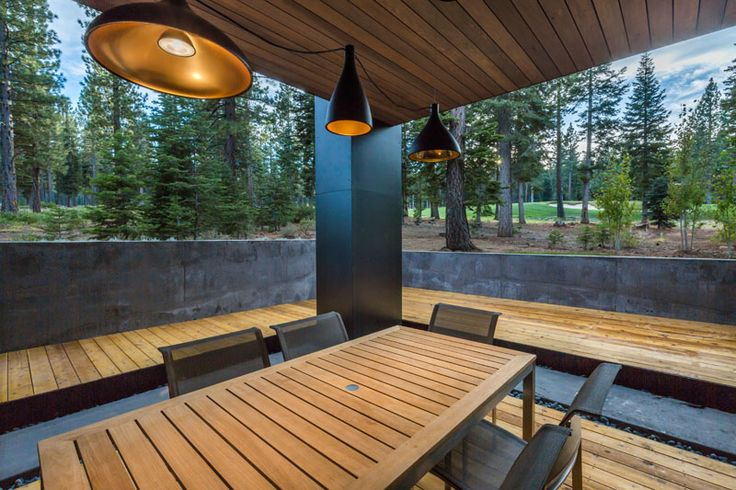 This modern home has a covered deck set up for outdoor dining.