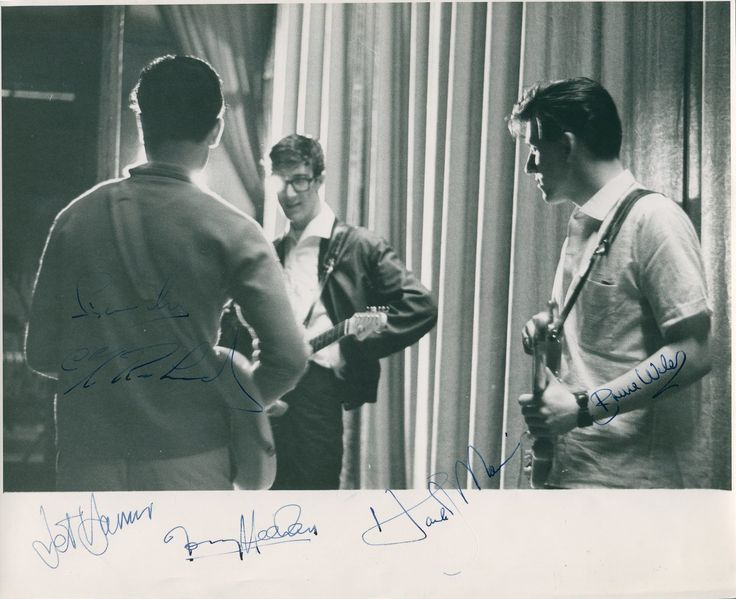 SHADOWS CLIFF RICHARD & THE: Vintage signed 9.5 x 8 photograph by Cliff Richard and The Shadows individually, comprising Hank Marvin, Bruce Welch, Jet Harris and Tony Meehan. The image depicts three of the band members standing in three quarter length poses together, each with their guitars. All have signed in blue fountain pen inks, most to clear areas of the image or the lower white border, only Richard's signature across a slightly darker area of the image.